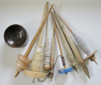 A selection of supported spindles, drop spindles, and a spindle bowl.