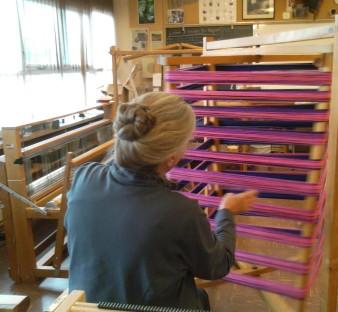 A weaver makes a warp in the Guild studio.