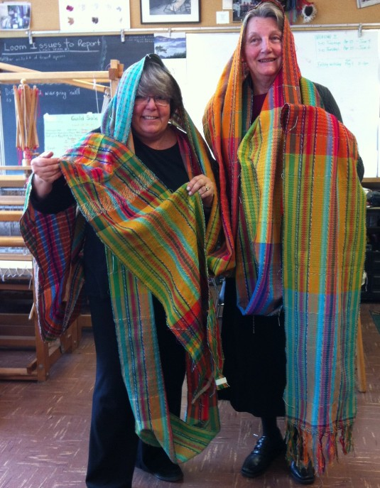 Guild members weave vibrant Woven Rainbow scarves in our studio.